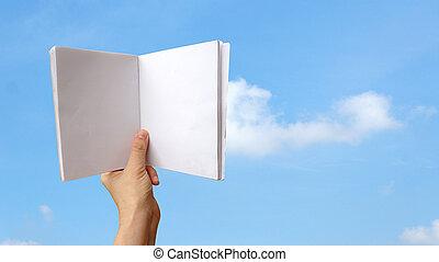 Hand holding blank white notebook over blue sky