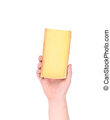 Hand holding block of parmesan cheese.