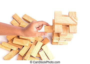Hand holding blocks wood game (jenga) isolated on white...