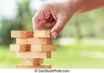 Hand holding blocks wood game (jenga) on blurred green...