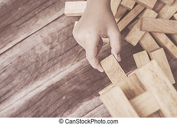 Hand holding blocks wood game (jenga) on wooden plank...