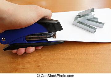 Hand holding blue stapler