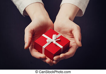 Hand holding box for a gift isolated on black