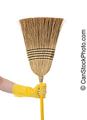A yellow gloved hand holding a corn broom on a white background