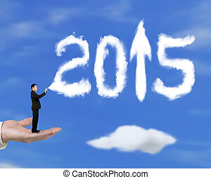 Hand holding businessman spraying 2015 arrow up clouds with sky