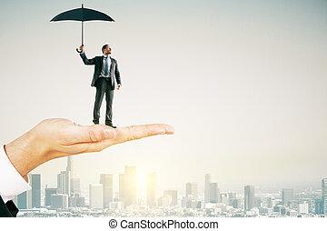 Hand holding businessman with umbrella