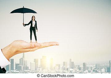 Hand holding businesswoman with umbrella