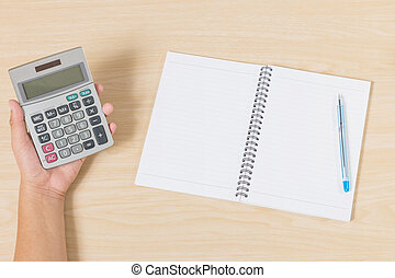 hand holding calculator and put pen and notebook on wood