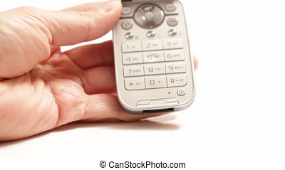 Hand holding cel phone and tapping buttons isolated on white...