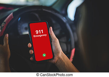 Hand holding cell phone with emergency number 911 in car