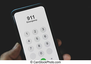Hand holding cell phone with emergency number 911 on black background
