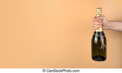 Hand holding champagne on a peach background with space to copy.