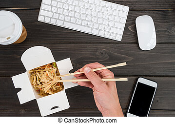 hand holding chopsticks with noodle and keyboard with...