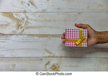 Hand holding christmas gift box. Christmas present in box at white wooden table.