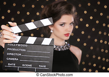 Hand holding cinema clap against the Fashion woman with sexy red