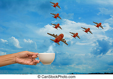 Hand holding coffee cup with airplane models on sky background
