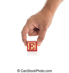 "Hand holding colorful alphabet blocks ""E"" isolated on white"