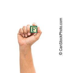"Hand holding colorful alphabet blocks ""F"" isolated on white background"