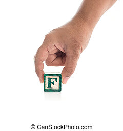 "Hand holding colorful alphabet blocks ""F"" isolated on white background"