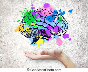 Hand holding colorful brain sketch on concrete background. Creative mind concept