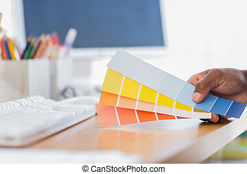 Hand holding colour charts in a modern office