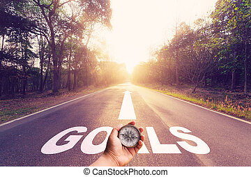 Hand holding compass on Empty asphalt road and Goals...