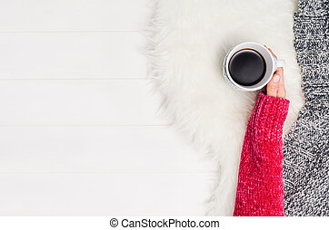 Hand holding cup of coffee. Top view with copy space