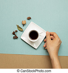 Hand holding cup of coffee with autumn dry leaves on green and brown background. flat lay, top view