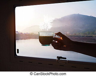 hand holding cup of hot coffee over glass window with mountian view