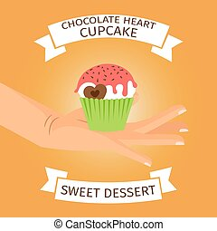 Hand holding cupcake with chocolate heart,