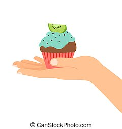 Hand holding cupcake with kiwi