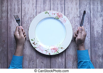 hand holding cutlery and empty plate on wooden background top down