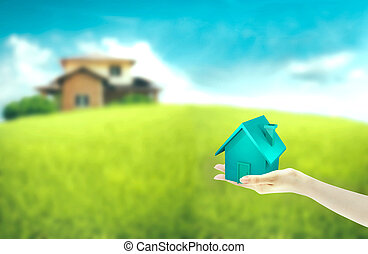 Hand holding dream house with house blurred in background