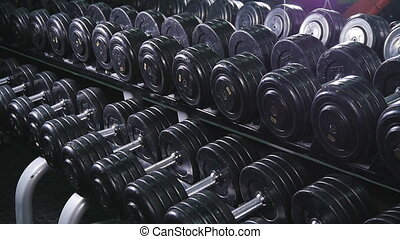 Hand holding dumbbell.Close up.Muscular arm in the gym....