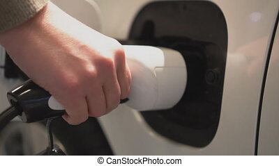Hand holding electric plug for charging electric car.