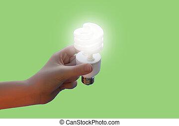 Hand holding energy saving CF light bulb on