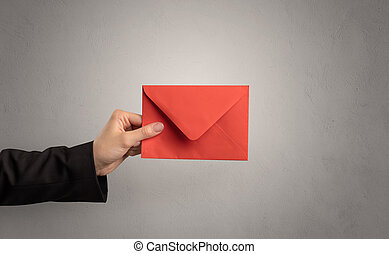 Hand holding envelope with empty wall background