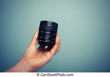 A hand is holding a set of extension tubes for macro photography