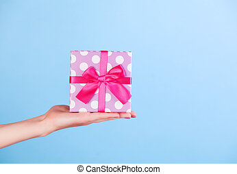 Hand holding gift on blue background.