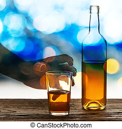 Hand Holding Glass and Bottle of Brandy
