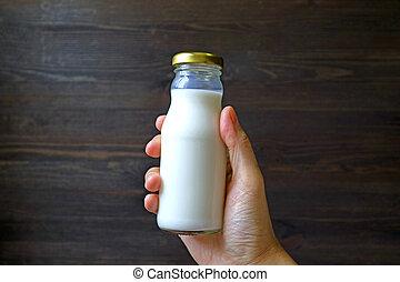 Hand holding glass bottle of milk against dark brown wooden wall