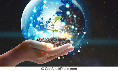 Hand holding globe with green plant growing ....