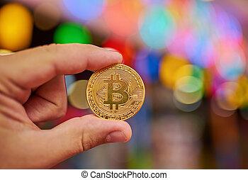 Hand holding golden Bitcoin virtual money.