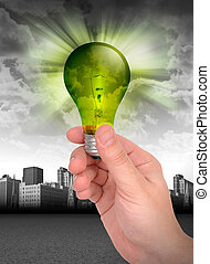 Hand Holding Green Energy Light Bulb - A hand is holding a...