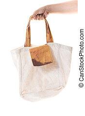 Hand holding grunge cotton bag on white background