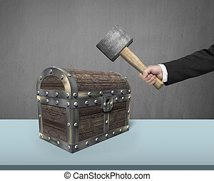 Hand holding hammer to hit old treasure chest