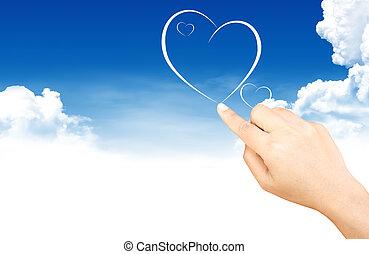 Hand holding heart shape cloud and blue sky - Hand holding...