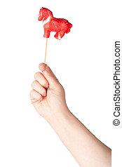 Hand holding horse shape lollipop