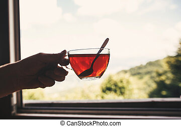 Hand holding hot tea in glass cup on background of  on beautiful landscape of woods and mountains. View from wooden window. Space for text. Travel and vacations