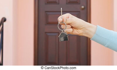 Female hand holding house key, real estate agent. Real estate concept